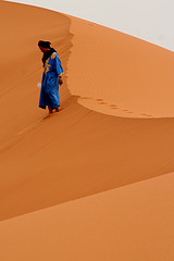 man walking on desert dunes
