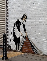 Sweeping maid stencil graffiti by Banksy