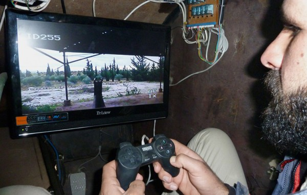 Syrian rebel fighter using games controller to aim gun turret
